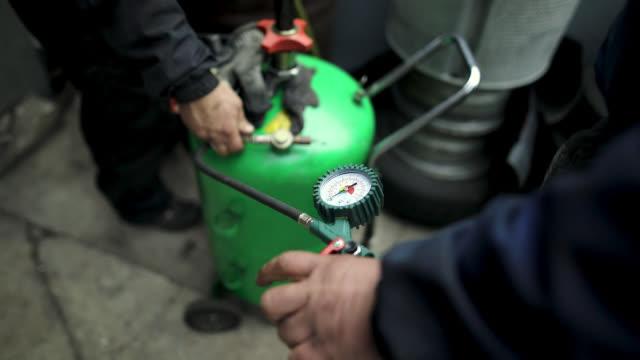 Man using gas compressor behind garage