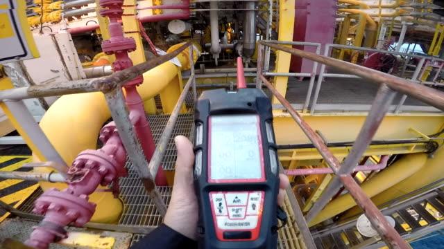 mann mit gasdetektor oder -instrument in verarbeitungsplattform oder anlage - wasserstoff stock-videos und b-roll-filmmaterial