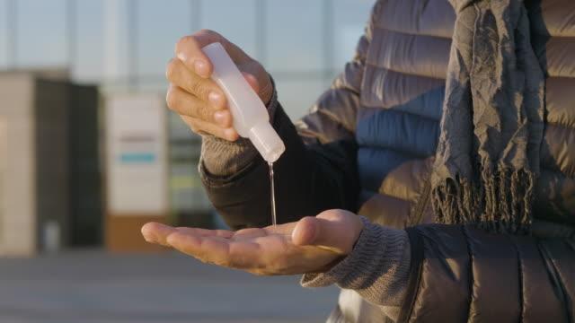vídeos y material grabado en eventos de stock de hombre usando desinfectante de manos y limpiando sus manos en la ciudad - hand sanitizer