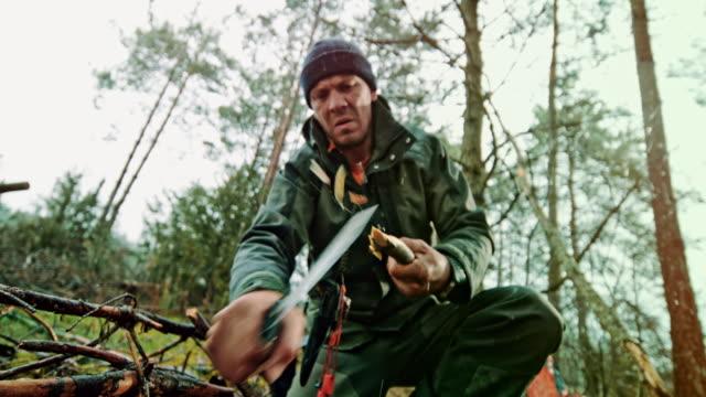 vidéos et rushes de slo mo homme utilisant son couteau pour aiguiser l'extrémité d'une branche dans le désert - étendue sauvage scène non urbaine