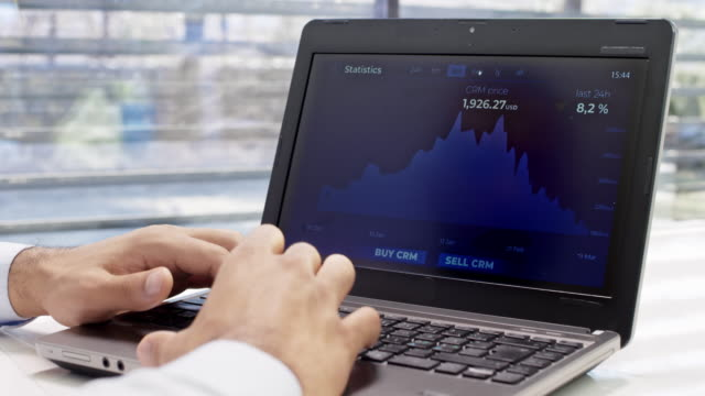 man using his laptop in the office to check the value of cryptocurrency - criptovaluta video stock e b–roll