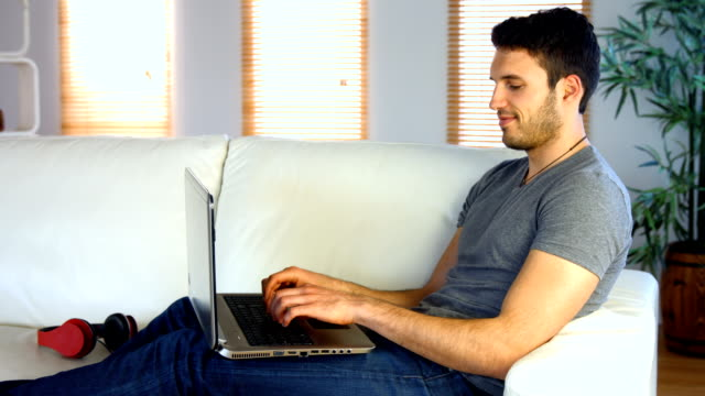 Man using his laptop on the couch video