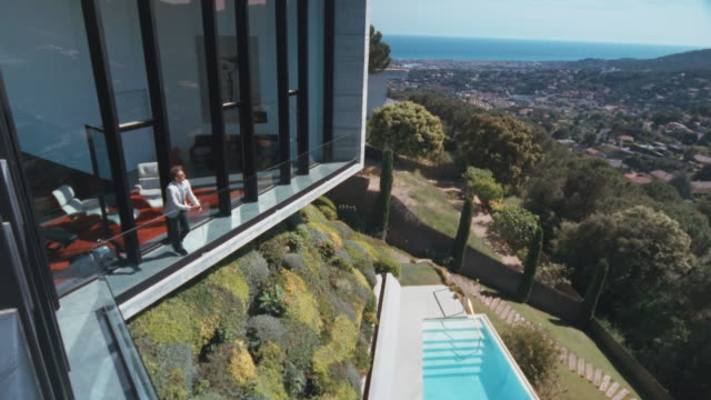 Man using his mobile phone A man standing outside of his luxury house. He looks over the city and the ocean while he is using his mobile phone.   wealth stock videos & royalty-free footage