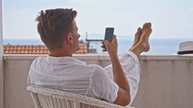 DS Man using his smartphone in a seaside hotel video