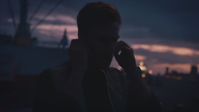 Man using in-ear headphones and smart watch Young man adjusting in-ear headphones for listening music at dusk. Handheld shot of handsome athlete is looking at smart watch. He is jumping and jogging at harbor in city. sportsperson stock videos & royalty-free footage