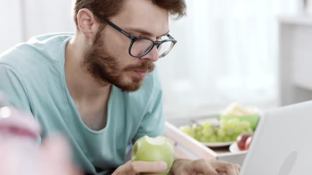 mann mit laptop und essen apfel - apple stock-videos und b-roll-filmmaterial