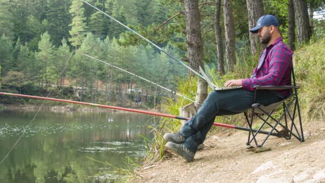 Man using laptop at campground fishing in lake video