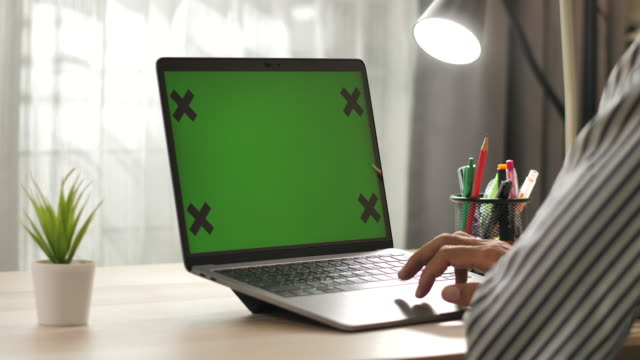 man using laptop green screen on desk at home - usare il laptop video stock e b–roll