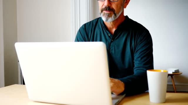 mann mit laptop im wohnzimmer 4k - männer über 40 stock-videos und b-roll-filmmaterial