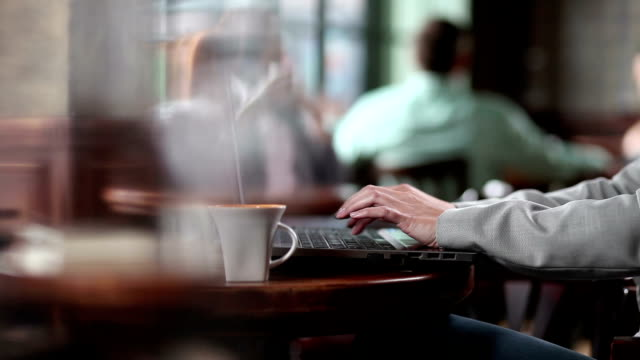 Man using laptop in the restaurant. video