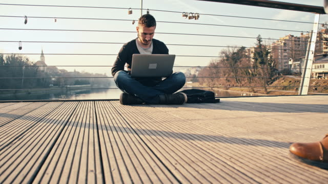 WS Man Using Laptop While Sitting On Bridge video