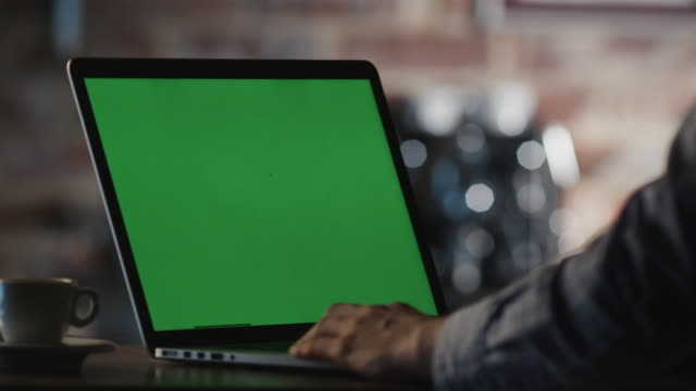 man using laptop with green screen in cafe. - usare il laptop video stock e b–roll