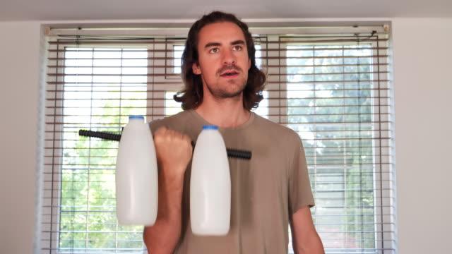 man som använder mjölk som vikter. - rådig bildbanksvideor och videomaterial från bakom kulisserna