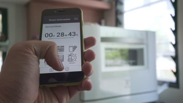vidéos et rushes de homme utilisant l'écran tactile d'application mobile pour contrôler la machine de lave-vaisselle - vaisselle picto