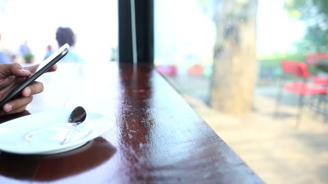 vídeos de stock e filmes b-roll de homem usando telefone móvel e beber café - coffee table