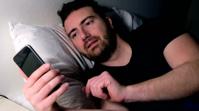 Man using mobile phone in bed video