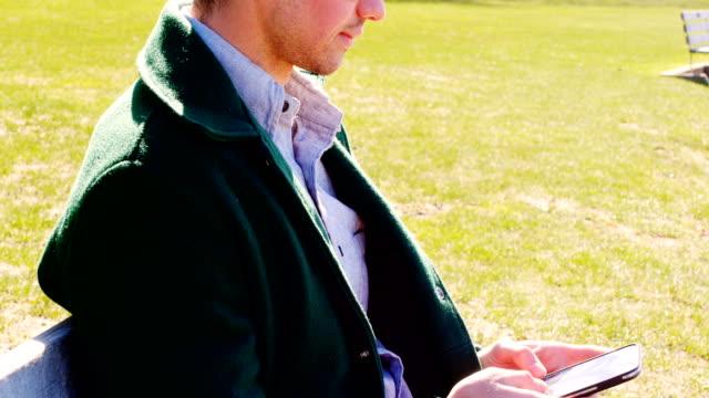 stockvideo's en b-roll-footage met man met mobiele telefoon in het park op een zonnige dag 4k - men blazer