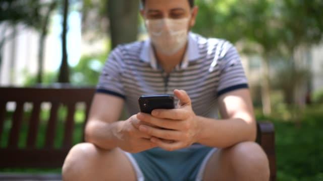 mann mit handy auf parkbank - mit gesichtsmaske - smartphone mit corona app stock-videos und b-roll-filmmaterial