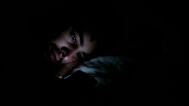 Man using phone at night, panning to alarm clock. video