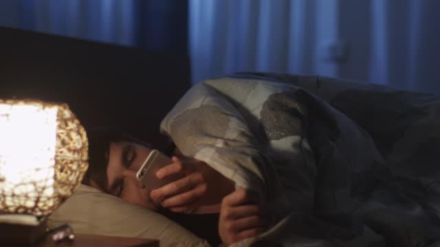 人は寝る前に電話を使用して、夜の光をオフに切り替える - スマホ ベッド点の映像素材/bロール