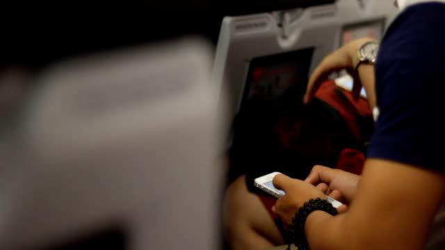 비행기에서 전화를 사용하는 남자 - airplane seat 스톡 비디오 및 b-롤 화면