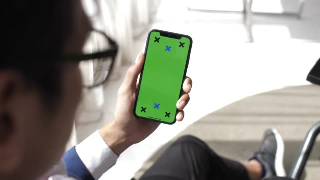 Man using phone with green screen hold in hands