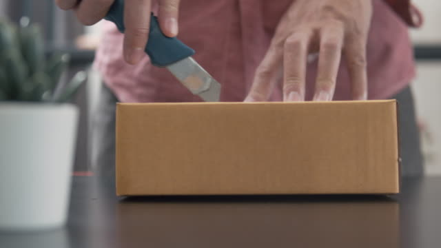 vídeos de stock e filmes b-roll de man using sharp knife cutting and opening box package from his online shopping - cardboard box