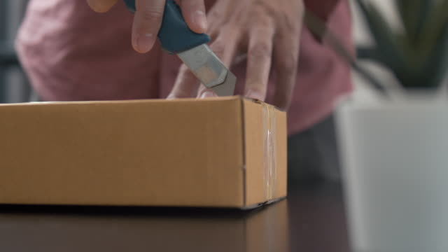Man using sharp knife cutting and opening box package from his online shopping