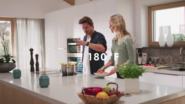 自宅で食べ物を調理しながらスマートデバイスを使用する男性 - 電化製品点の映像素材/bロール