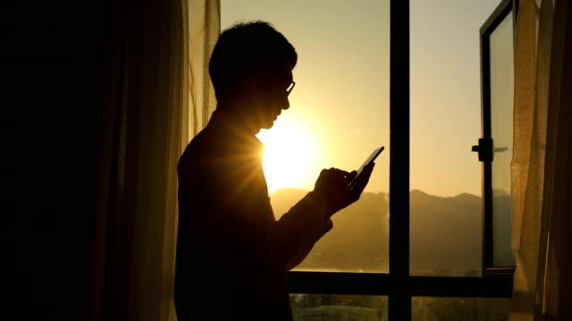 夕暮れ時にスマートフォンを使用する男 - コントロール点の映像素材/bロール
