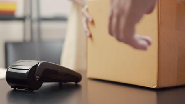 男子使用智慧手機非接觸式支付技術支付包裹發貨單。 - postal worker 個影片檔及 b 捲影像