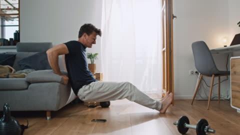 ds man che usa lo smartphone per fare alcuni esercizi a casa - allenamento video stock e b–roll