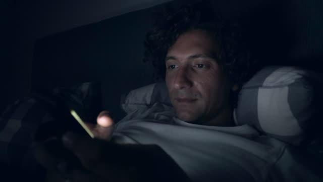 夜遅くにスマート フォンを使用している人。 - スマホ ベッド点の映像素材/bロール