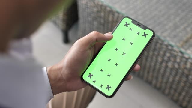 man använder smart telefon med grön skärm uppvisning - skrollning bildbanksvideor och videomaterial från bakom kulisserna