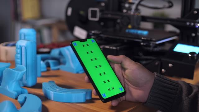 man använder smart telefon med grön skärm på skrivbordet i 3d-skrivare labroratory - telefonmeddelande bildbanksvideor och videomaterial från bakom kulisserna