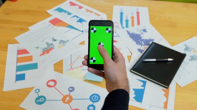 Man using smart phone with green screen on office desk, work space, information look up Man using smart phone with green screen on office desk, work space, information look up workbench stock videos & royalty-free footage