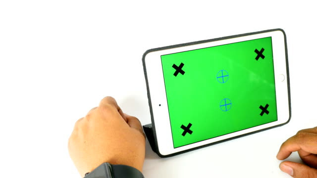 Man using smart watch and tablet with green screen on white background, chroma key video