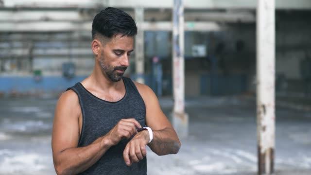 man använda smart watch-klocka under träningen i övergiven lagerlokal - människokroppsdel bildbanksvideor och videomaterial från bakom kulisserna