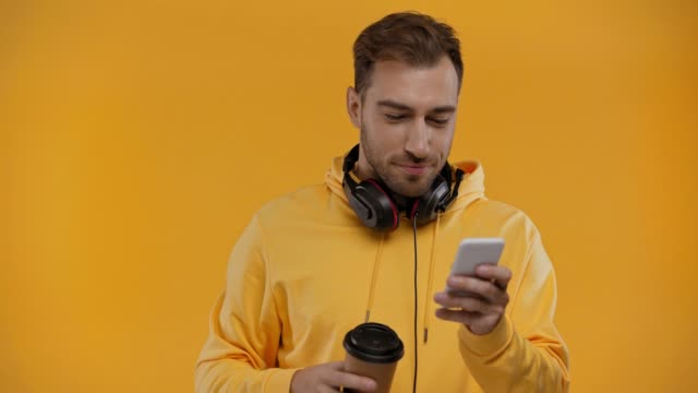 man using smartphone and drinking coffee isolated on yellow man using smartphone and drinking coffee isolated on yellow background color stock videos & royalty-free footage