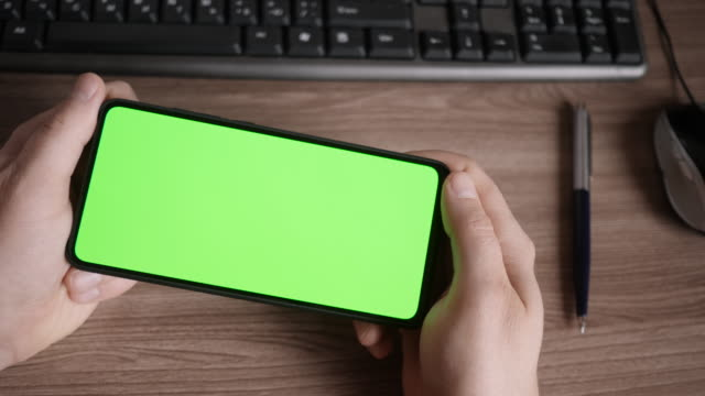 Man Using Smartphone  in Horizontal Mode with Green Mock-up Screen, Doing Swiping, Scrolling Gestures. Guy Mobile Phone, Internet Social Networks Browsing News, Financial Reports. Point of View Camera