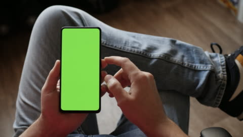 vídeos de stock, filmes e b-roll de homem usando smartphone no modo vertical com tela de mock-up verde, fazendo deslizar, rolar gestos. guy mobile phone, internet redes sociais navegando notícias, relatórios financeiros. câmera ponto de vista. - smartphone