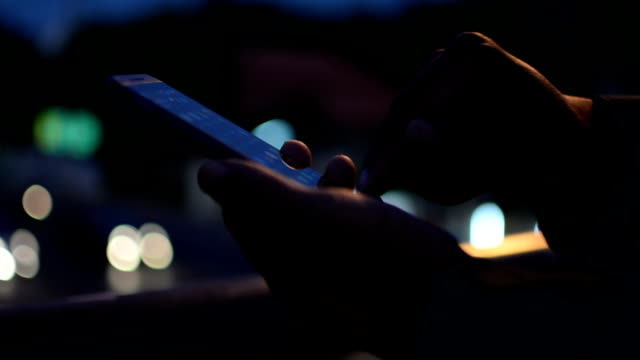 Man using smartphone, night. video