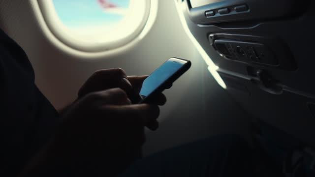 man using smartphone on a plane, - wygodny filmów i materiałów b-roll