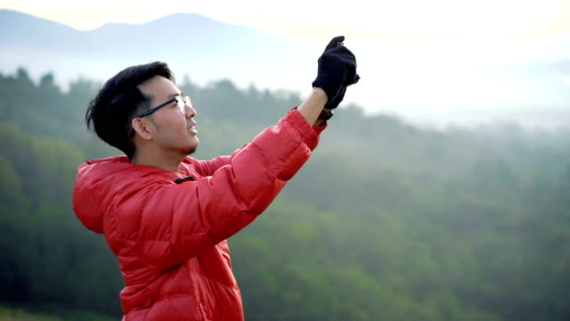 Man using smartphone to take a photo and video at the top of mountain with river view video