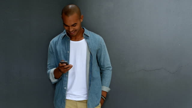 Man using smartphone Young african man leaning against a grey wall using mobile phone. Portrait of a happy laughing guy texting a phone message. Man in casual typing and reading a message on cell phone with copy space. leaning stock videos & royalty-free footage