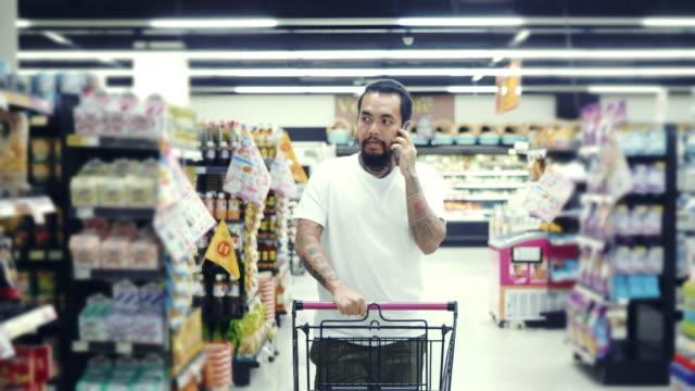 vídeos y material grabado en eventos de stock de un hombre usando smartphone, caminando más allá de la sección de productos frescos de la tienda. - snack aisle