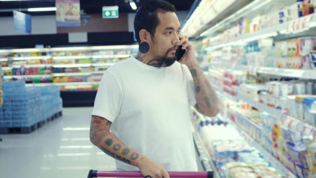 A Man Using Smartphone, Walking Past Fresh Produce Section of the Store. Young man talking on cell phone and shopping for produce in grocery store snack aisle stock videos & royalty-free footage