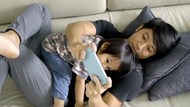 Man using smartphone with baby laying on chest. video