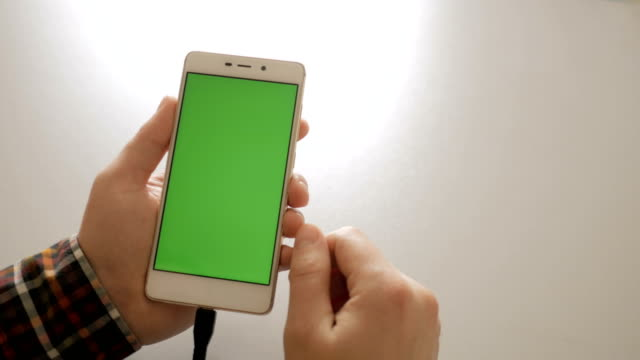 Man using smartphone with green screen . Smart phone charging with USB charger close-up connection in hands - USB data cable connecting on modern gadget. Chroma key. Green screen.