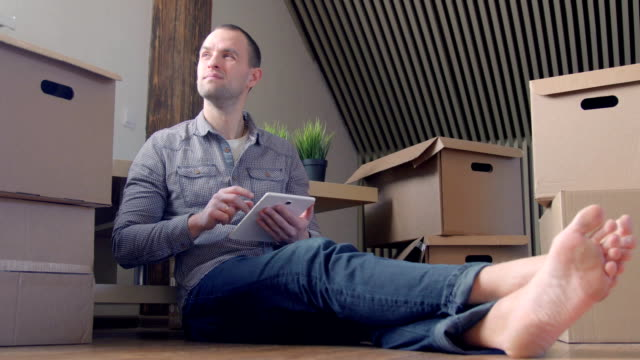 man använder surfplatta i nya hushus efter flytten. - bordsjordglob bildbanksvideor och videomaterial från bakom kulisserna